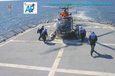 """Los """"camisas azules"""" a punto de """"trincar"""" (amarrar) los esquies del helicóptero a la cubierta del buque./The ship's crew about to secure the helicopter's skies to the deck of the """"Artigas""""."""